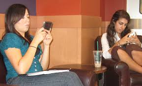 Two women text messaging on their cell phones in a coffee shop on the campus of California State University, Fullerton.